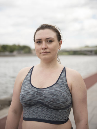 Portrait of woman standing against water