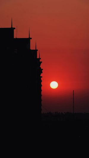 Low angle view of silhouette building against orange sky