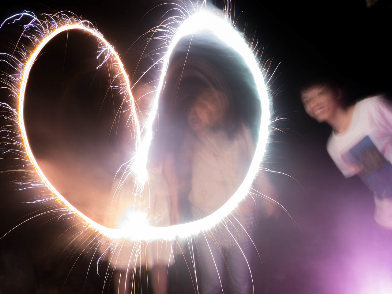 real people, one person, long exposure, illuminated, night, leisure activity, men, motion, lifestyles, sparkler, playing, standing, technology, women, indoors, young women, young adult, close-up, people