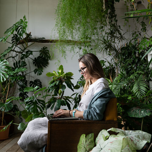 Woman sitting on chair by plants