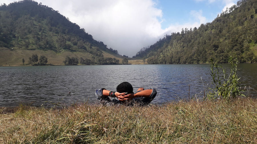 Man lying on grass by lake against mountains and sky