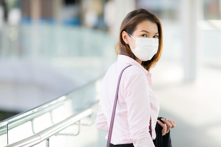 Portrait of businesswoman wearing mask standing by railing outdoors