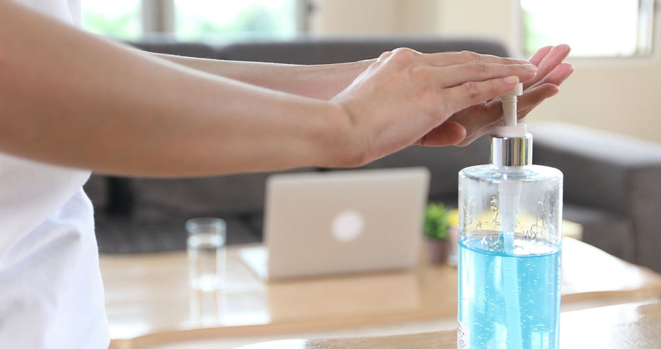 Midsection of man holding glass bottle on table