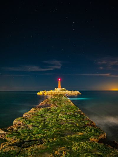 Lighthouse By Sea Against Sky At Night