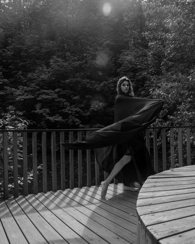 Woman standing by railing in forest