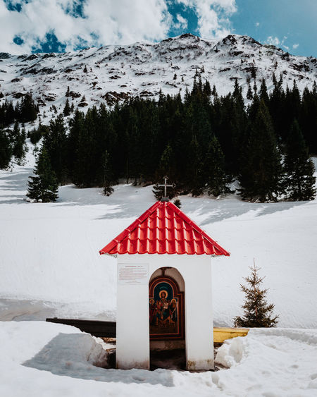 Church on snow covered road against mountain during winter