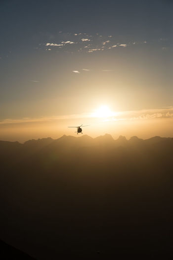 Silhouette Helicopter Against Sky During Sunset