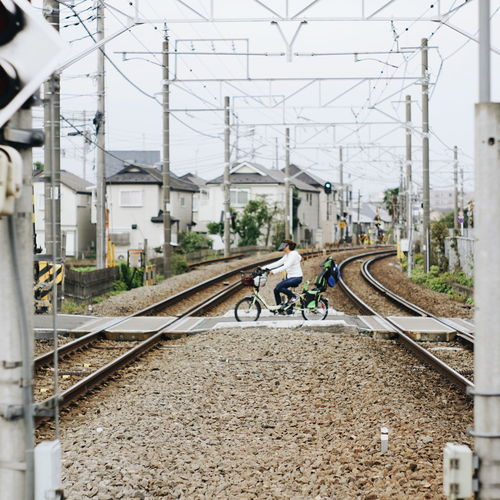 Cyclists crossing the railroad Transportation Rail Transportation Track Railroad Track Mode Of Transportation Architecture Bicycle Cable Built Structure Land Vehicle Building Exterior Day Electricity Pylon Men Electricity  Real People Power Line  City Nature Connection Riding Outdoors Power Supply