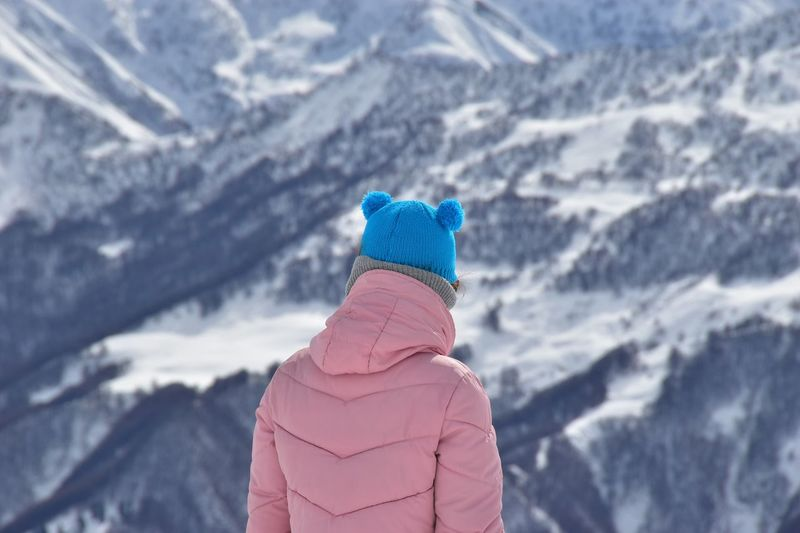 Rear view of woman standing against snowcapped mountain