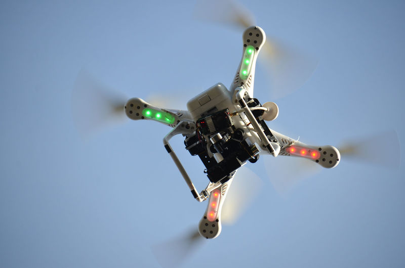 Low angle view of flying drone against clear sky
