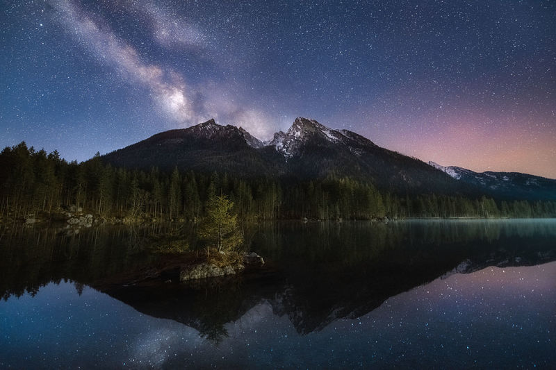 Scenic view of lake by mountains against sky at night