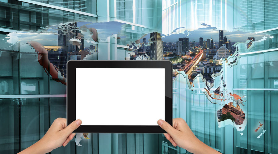 Cropped hands of woman holding digital tablet against digitally composite world map