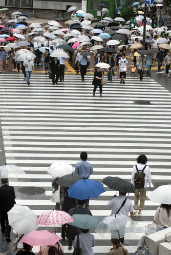 People crossing street during rainy season