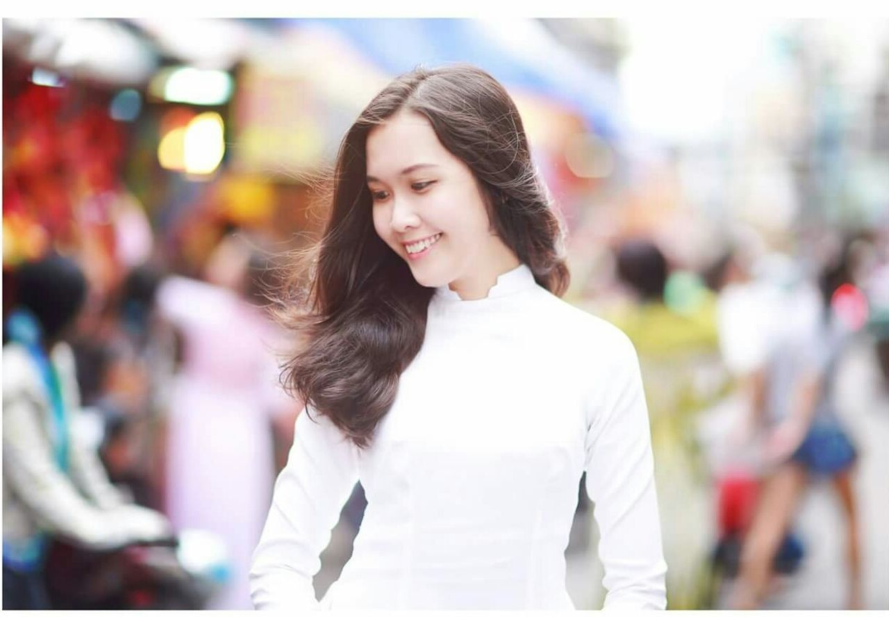 incidental people, smiling, focus on foreground, waist up, young adult, happiness, standing, casual clothing, one person, young women, outdoors, day, cheerful, beautiful woman, real people, portrait, one young woman only, one woman only, adult, adults only, people