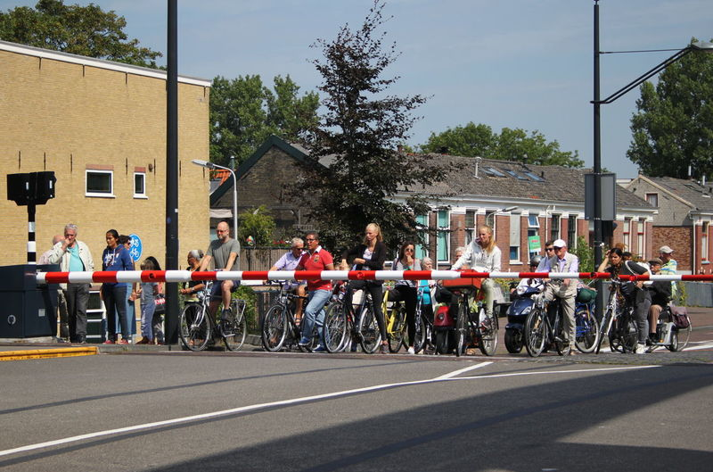 Delft, Netherlands Summer 2015 Bicycles City Day Large Group Of People Outdoors Real People Street Waiting For The Bridge To ın A Row