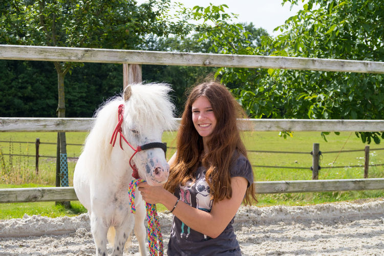 Portrait of happy woman with pony standing in ranch