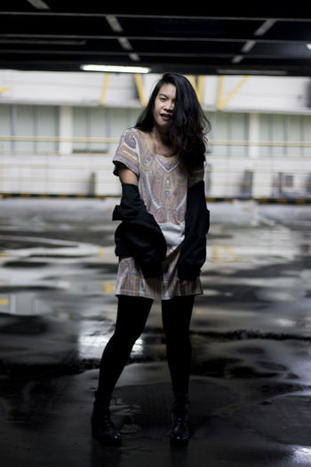 Full length of young woman standing on wet floor in parking lot