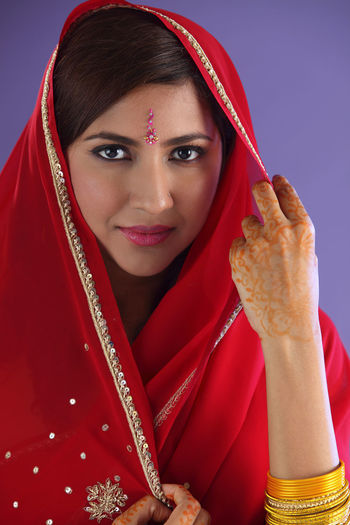 Portrait of beautiful indian woman in red sari against purple background