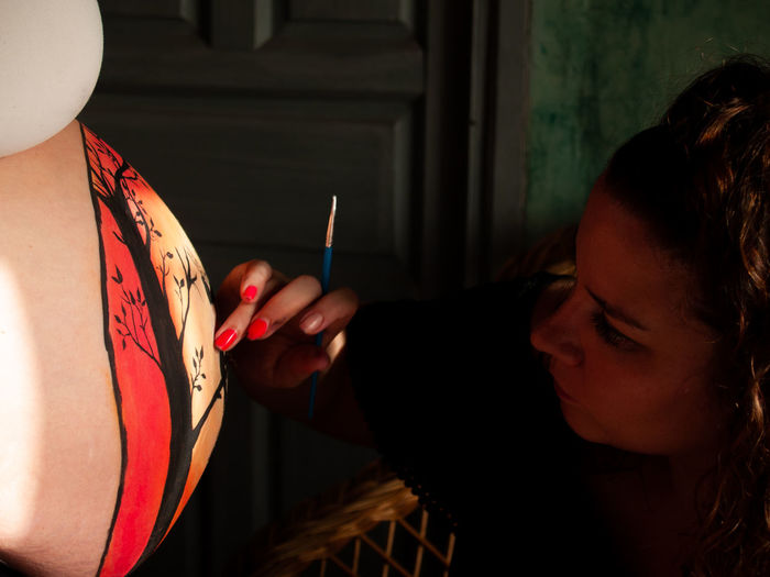 Woman painting on pregnant friend belly