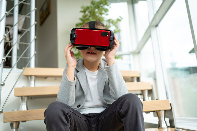 Portrait of boy holding mobile phone while sitting on laptop