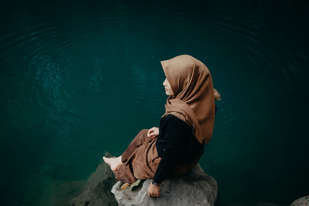 High angle view of woman wearing hijab sitting on rock by lake