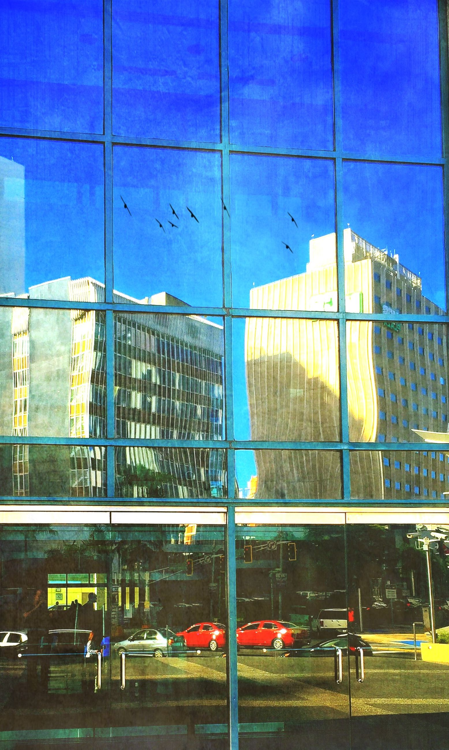 architecture, built structure, building exterior, city, glass - material, transportation, modern, blue, window, building, reflection, land vehicle, office building, mode of transport, transparent, city life, street, road, day, car