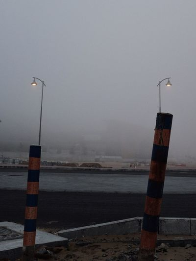 Street lights by road against sky during foggy weather