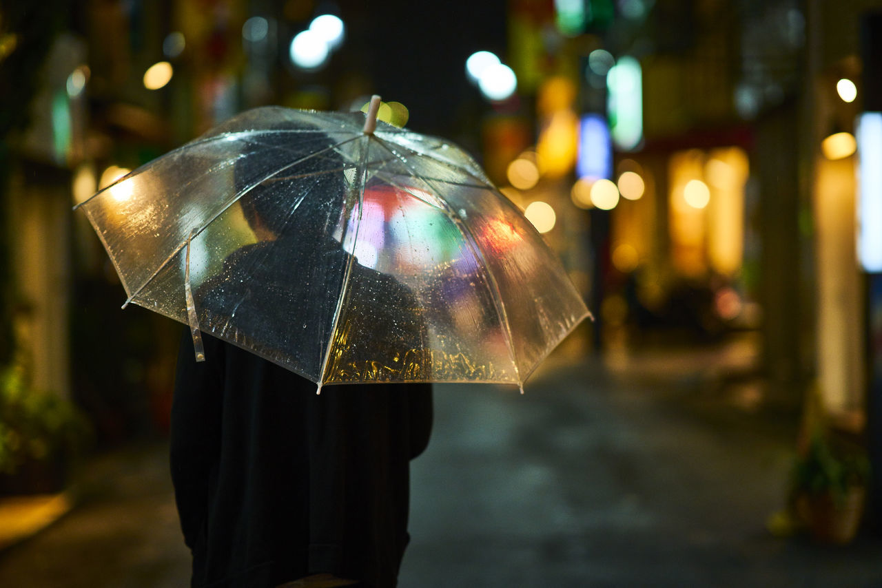 Rear view of person holding umbrella at night