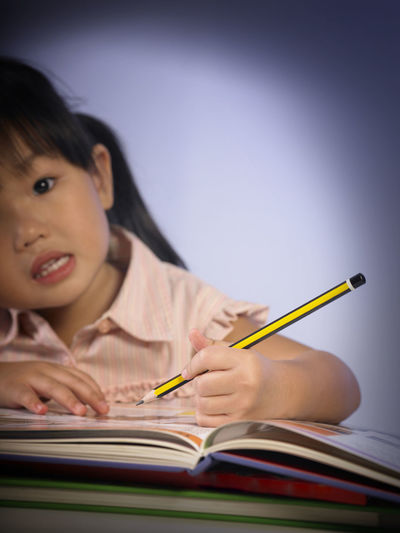 Close-up of cute girl writing on book at table against wall
