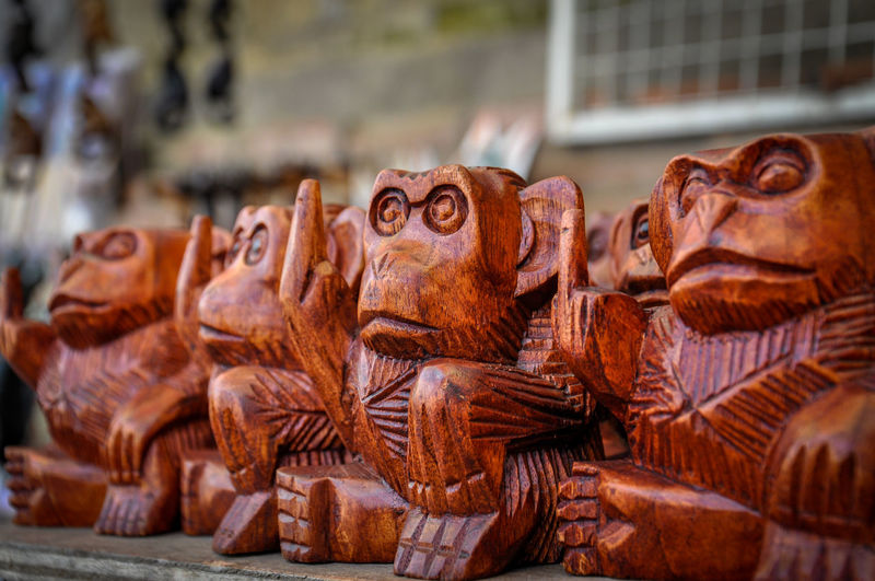 Close-up of wooden monkey figurines for sale in market