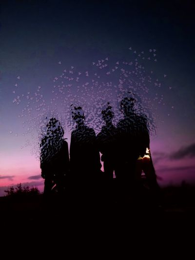 Silhouette people against sky at night