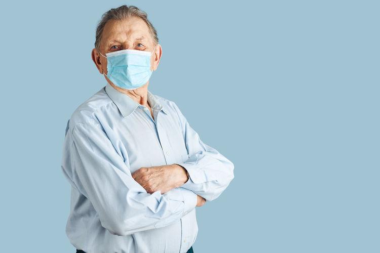 Portrait of man wearing mask against blue background