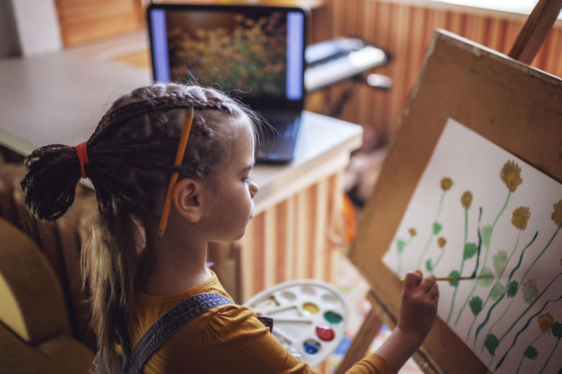Side view of girl painting at home