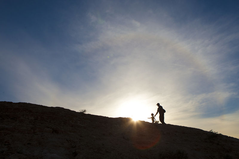 Silhouette man on mountain against sky during sunset