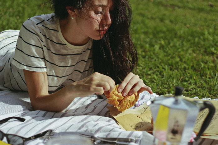 Woman having croissant while reading papers at park