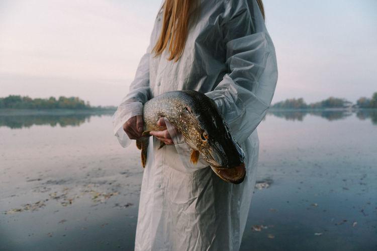 Midsection of young woman holding fish