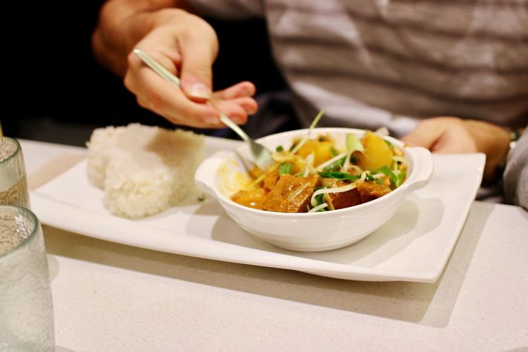 Close-up of hand eating food at table