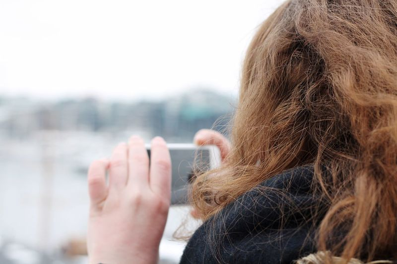 Close-Up Of Woman Using Mobile Phone In City
