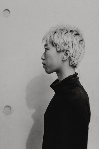 Portrait of young man looking away against wall