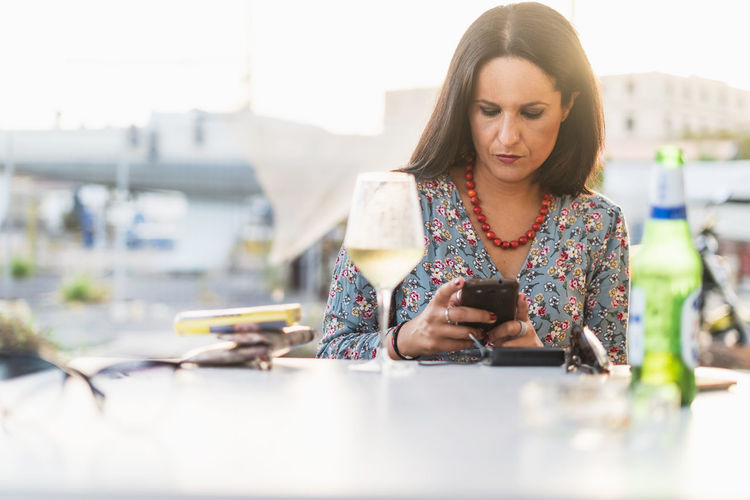 Mid adult woman using mobile phone while sitting at table