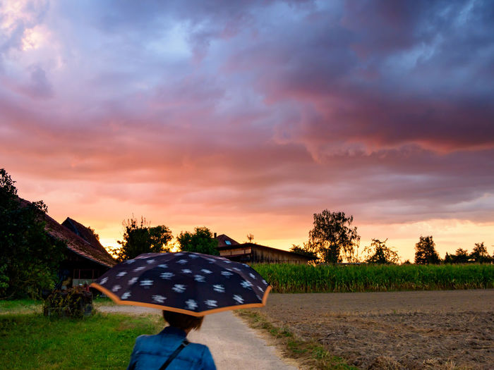 Woman with umbrella standing on street during sunset