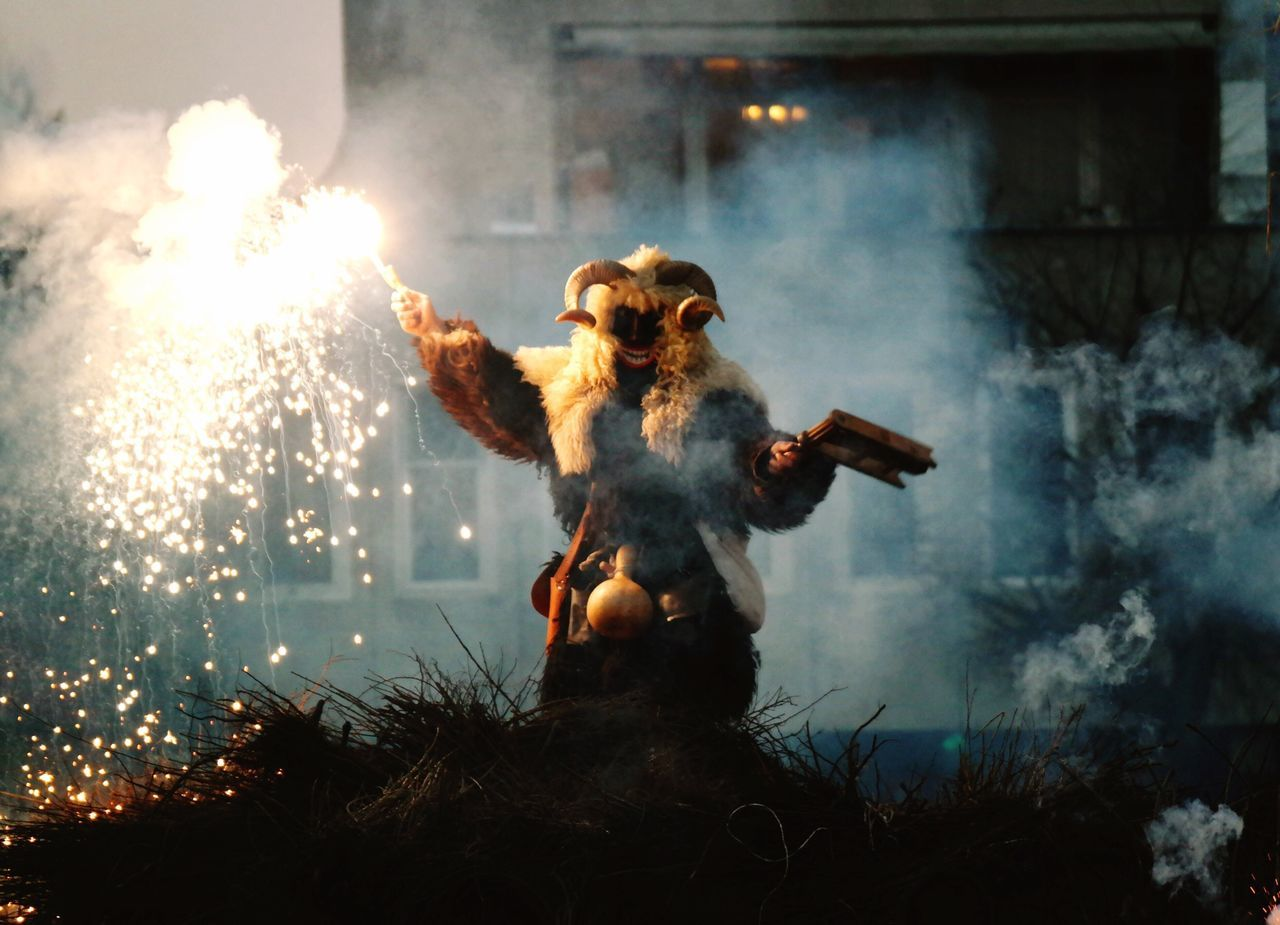Person in costume holding lit firework during busajaras