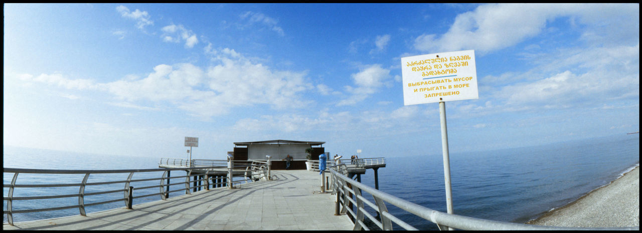 Information sign by pier on sea against sky
