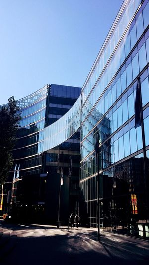 Gemini Streetphotography Streetphoto_color Building Exterior Built Structure Architecture Modern Glass - Material City Reflection Office Building Clear Sky Glass Urban Skyline Outdoors Light And Shadow Urbanphotography Berlin Sunlight Modern Architecture Flags Curves And Lines Capture Berlin Twins View From Behind Embrace Urban Life