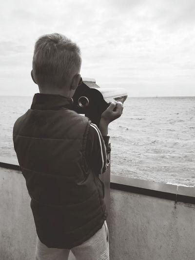 Rear view of boy looking at sea through binoculars against sky