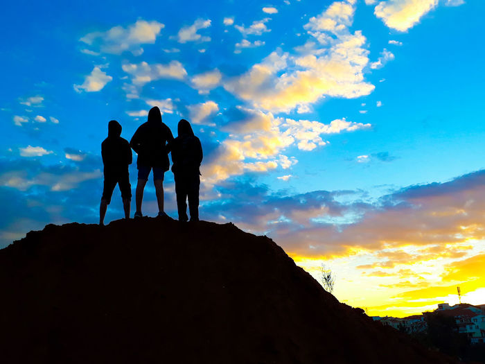 Silhouette men standing on rock against sky during sunset