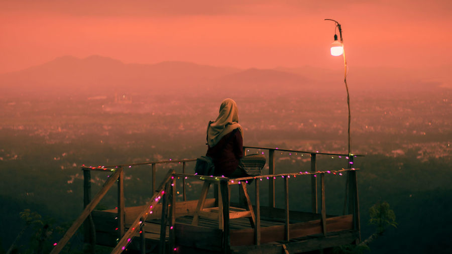 Rear view of woman sitting on rooftop by railing against sky during sunset