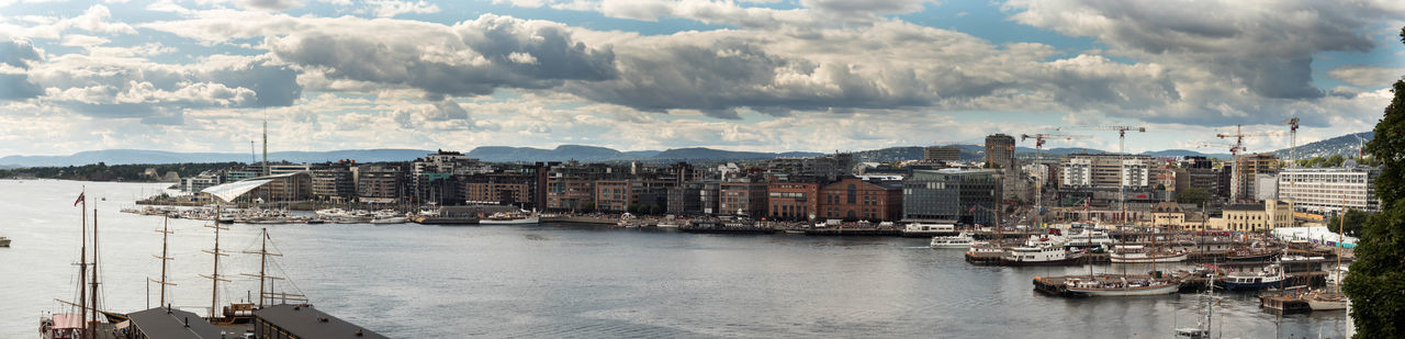 Panoramic View Of Oslo Port In City By Sea Against Cloudy Sky