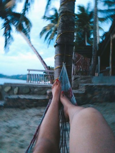Low section of person relaxing on hammock