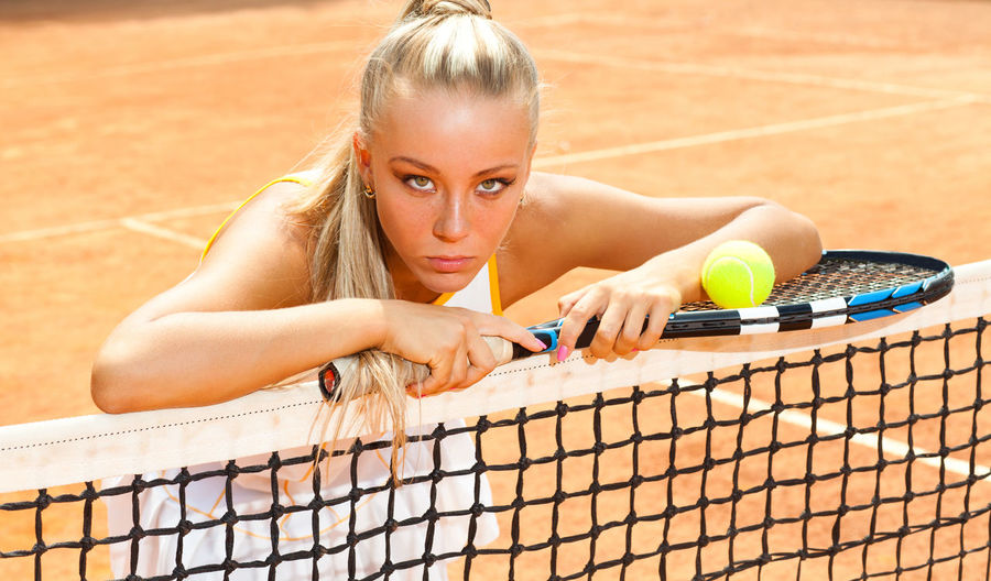 Young woman in a tennis dress and with the racket in her hand leaning on the net One Person Lifestyles Sport Women Leisure Activity Real People Young Adult Young Women Front View Portrait Tennis Day Looking At Camera Athlete Playing Adult Beauty Hair Hairstyle Beautiful Woman